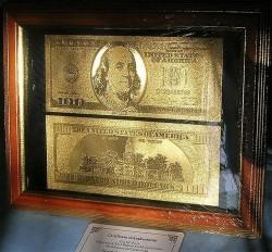 Золотая купюра 100 долларов США в рамке